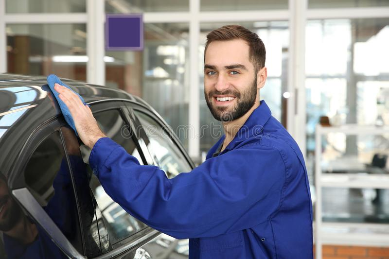 Portrait of worker cleaning automobile with rag. At car wash royalty free stock photography