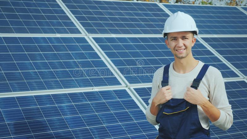 Portrait of a worker in a helmet, looking at the camera, stands against the background of a row of solar panels royalty free stock photos