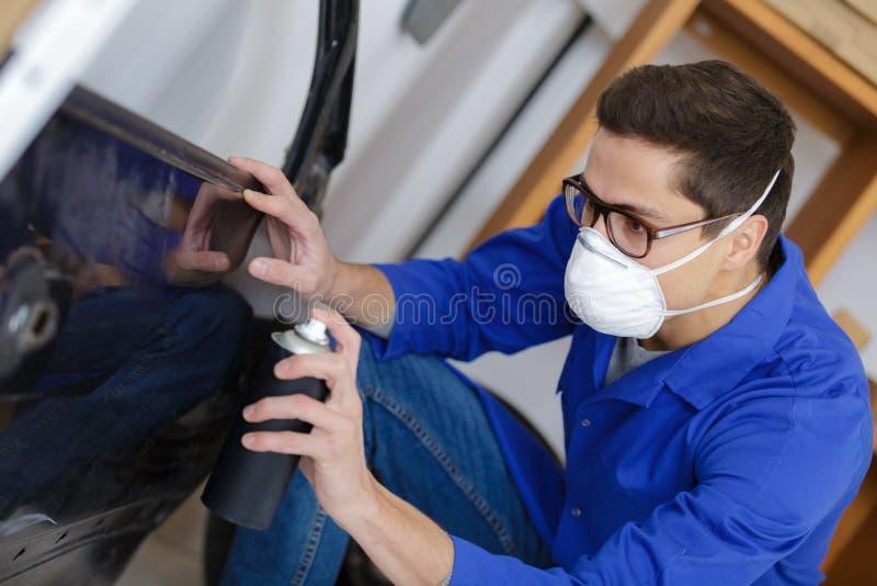 Portrait worker painting car stock image
