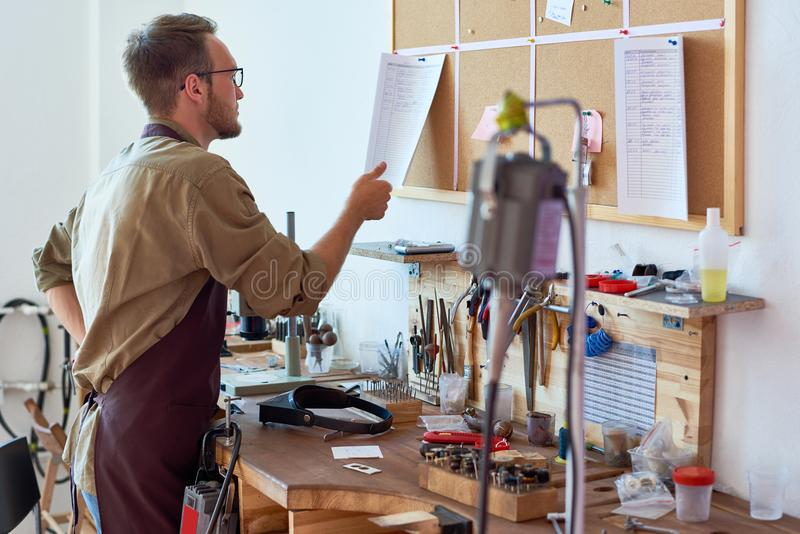 Man in Crafting Workshop. Portrait of workman in apron checking order documentation on board above workshop table royalty free stock image