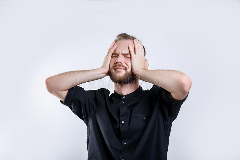 Portrait of worried bearded young man with closed eyes .Stressed young businessman royalty free stock photo