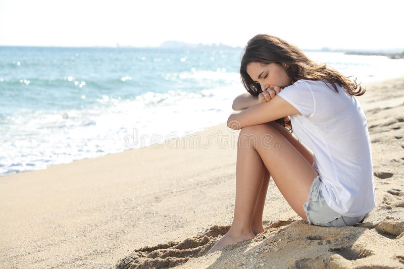 Portrait of a worried girl sitting on the beach stock image
