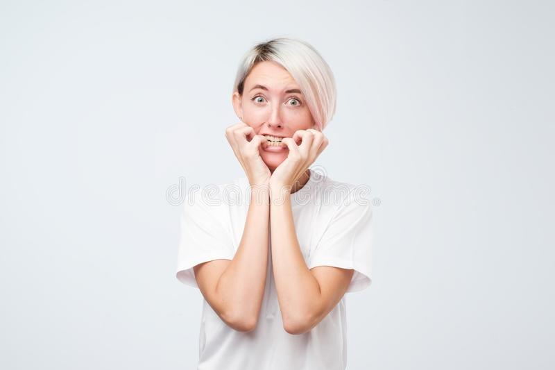 Portrait of worried scared woman with dyed short hair looking at camera, studio shot. stock photography