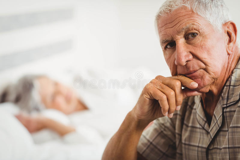 Portrait of worried senior man sitting on bed stock image
