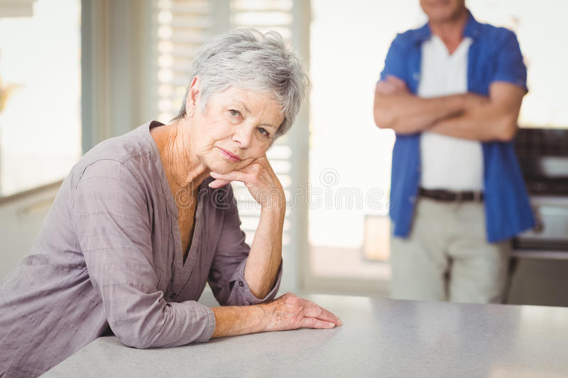 Portrait of worried senior woman with man standing in background stock image