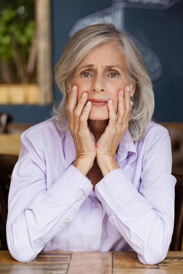 Portrait of worried senior woman sitting at table royalty free stock images