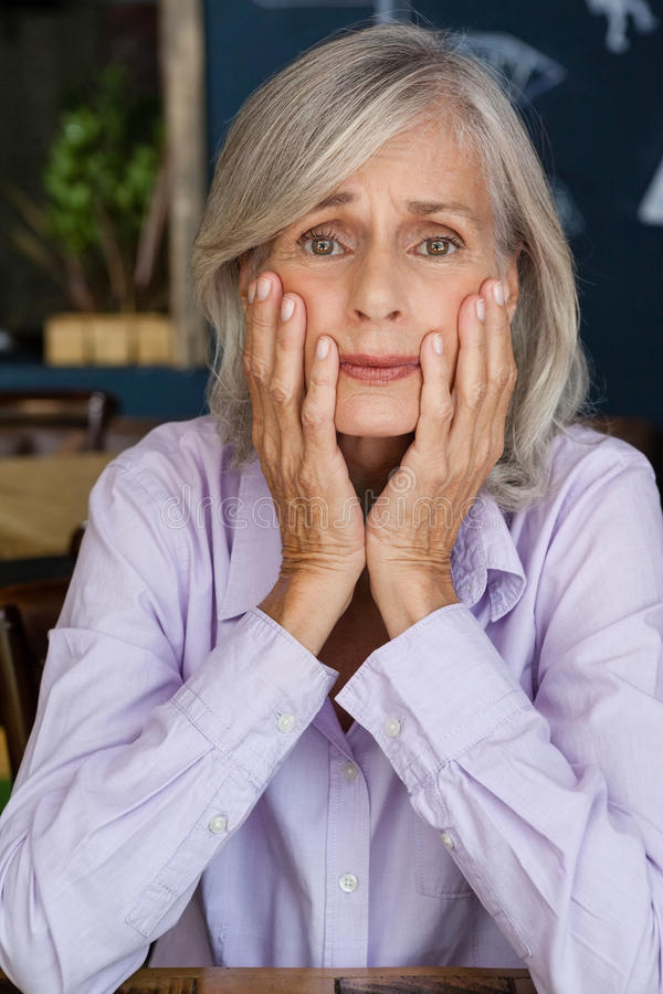Portrait of worried senior woman at table stock images