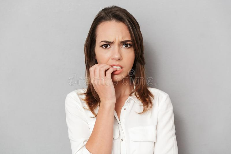 Portrait of a worried young business woman biting nails royalty free stock photography