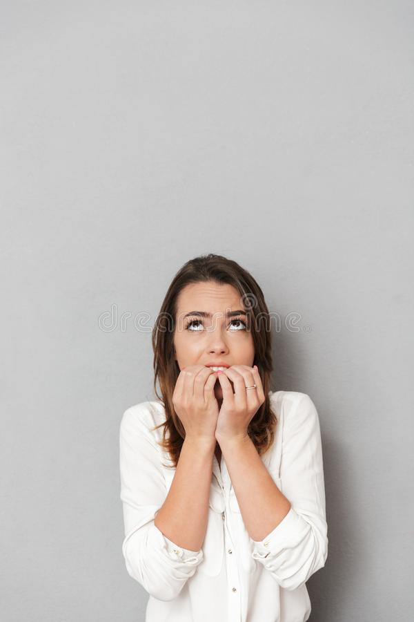 Portrait of a worried young business woman biting nails royalty free stock image