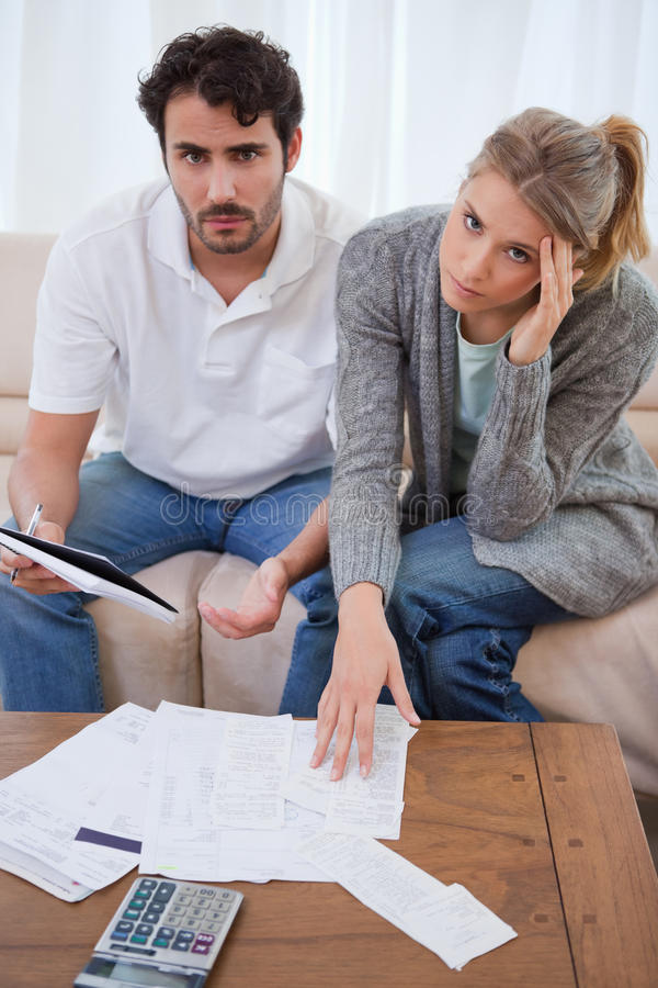Portrait of a worried young couple looking at their bills royalty free stock photos