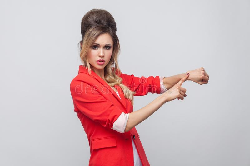 Portrait of worry beautiful business lady with hairstyle and makeup in red fancy blazer, standing and touching her hand to show. Time gesture. indoor studio stock photos