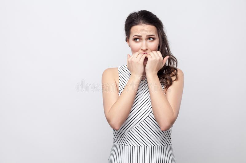 Portrait of worry beautiful young brunette woman with striped dress standing, looking away and bitting her nails with stressed royalty free stock images