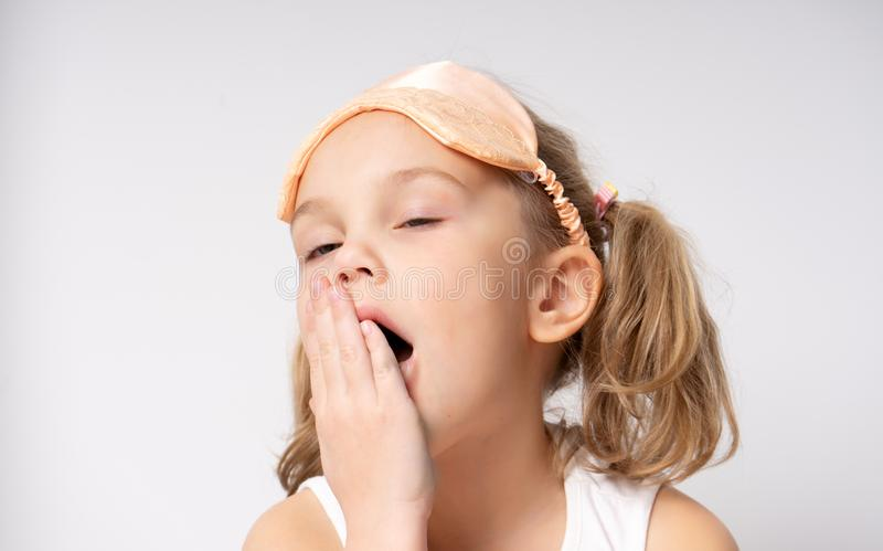 Portrait of yawning little girl in sleaping mask Sleep concept royalty free stock images
