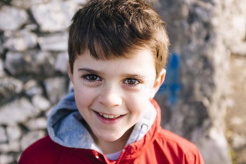Portrait of 9 year old boy with red jacket outside. As a big rock background stock images