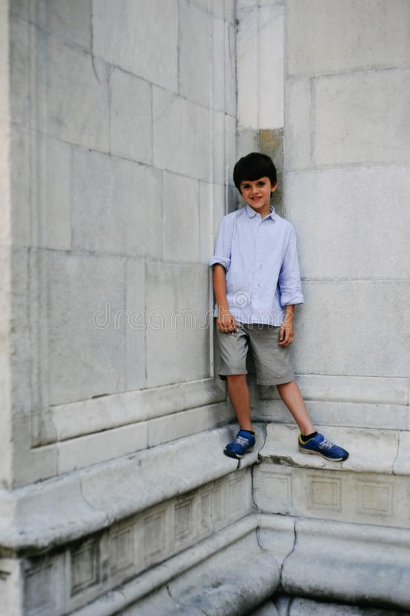 Portrait of 10 year old child with stone wall background of a ca. Thedral stock photo