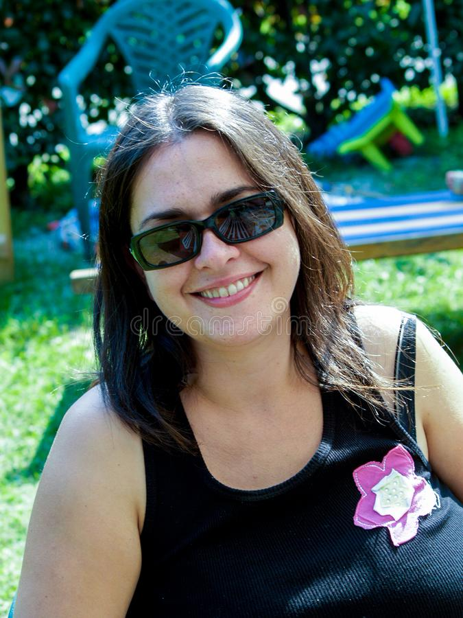Portrait of 30 year old girl with dark glasses alone, smiling an royalty free stock image