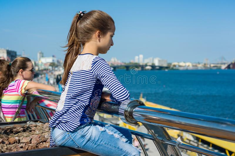 Portrait of a 10 year old girl in a profile. Background of a river in a modern city, blue sky. royalty free stock image