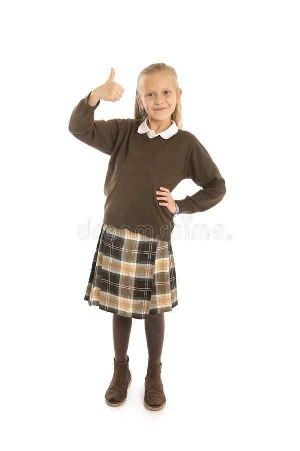 Portrait of 7 or 8 years old beautiful and happy schoolgirl female child in school uniform smiling cheerful isolated on white back. Ground in children education royalty free stock image