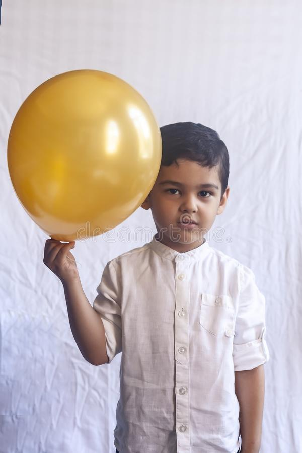 Portrait of 5-6 years old boy with balloon. Adorable middle eastern kid holding a golden balloon. Celebrating, holiday concept stock photo