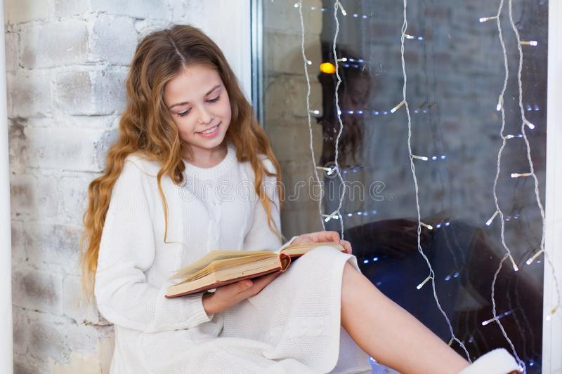 Portrait of 10 years old child reading book on the window on christmas. stock image