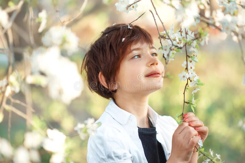 Portrait of 7 years old cute stylish short haired smiling girl in white shirt sniffing flower in blooming garden in spring. Short. Haircut for girl. Allergy stock images