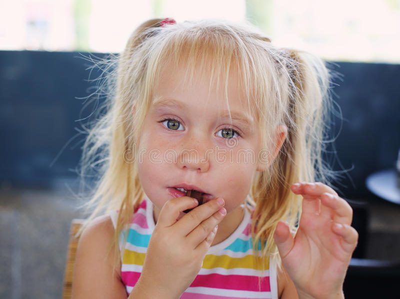 Portrait of 5 years old girl. Sitting in the cafe royalty free stock image