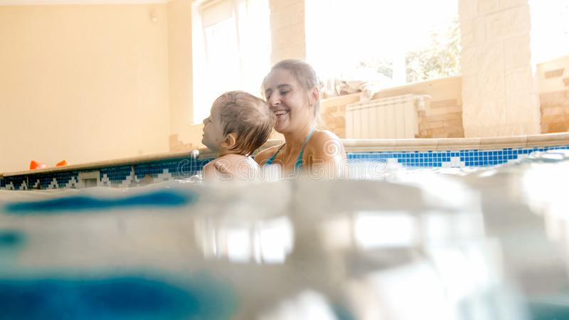 Portrait of 3 years old toddler boy with young mother swimming in the indoors pool. Child learning swimming and doing royalty free stock photo