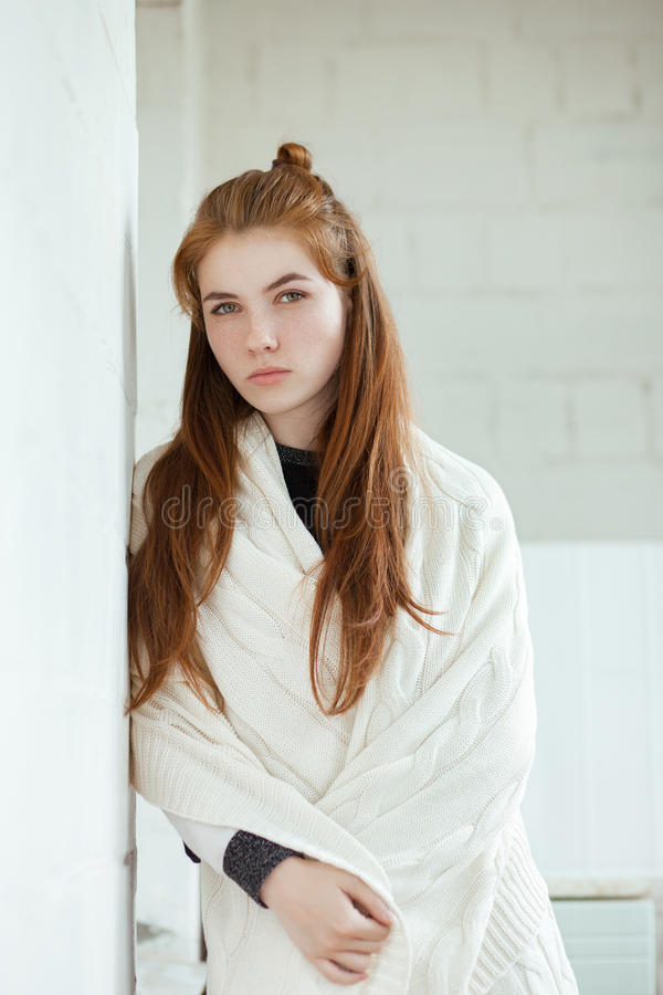 Portrait of young adorable redhead woman wrapped in a white knitted blanket posing near white wall indoor natural light royalty free stock image