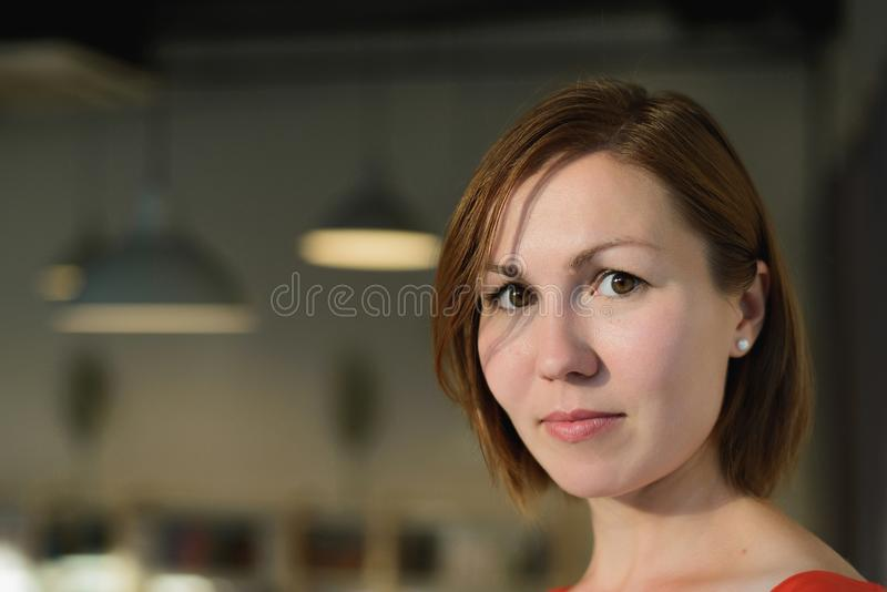 Portrait of young adult asian woman with brown bob hair on blurred interior cafe background. Horizontal lifestyle stock photo image with copy space royalty free stock images
