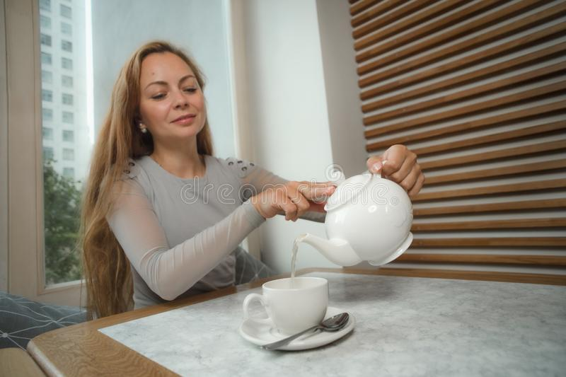 Beautiful young woman pouring tea into cup stock images