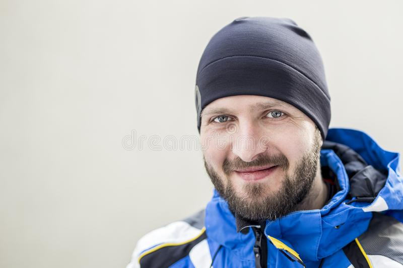 Portrait of young adult confident bearded man wearing warm sport clothes and hat at cold winter day. Smiling happy sportsman at st royalty free stock photo