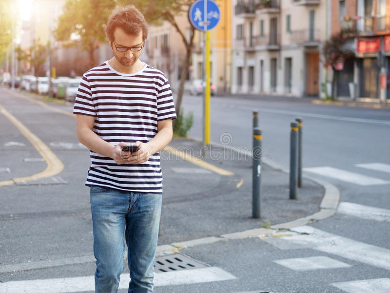 Portrait of young adult man crossing road inattentively royalty free stock images