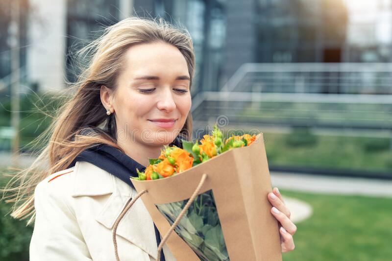 Portrait young adult smiling classy woman model hand holding authentic fresh orange spray roses flower bouquet wrapped in craft. Paper bag on city urban street royalty free stock image