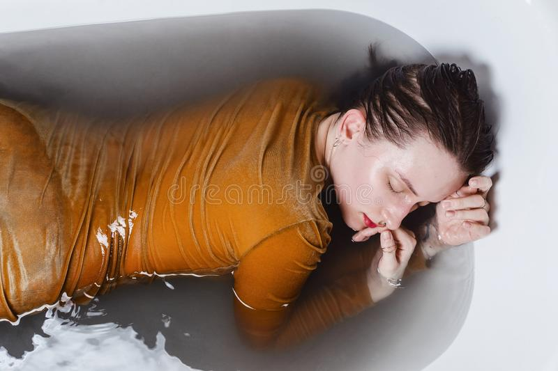 Portrait of young adult woman lying in bathtub filled with charcoal water royalty free stock images