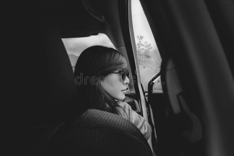 Portrait of Young Adult Woman sitting in Car on Driver Seat. Looking Outside Window stock images