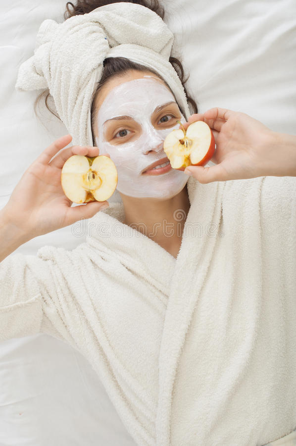 Portrait of a young adult woman in the spa salon with Facial krem Mask royalty free stock photography