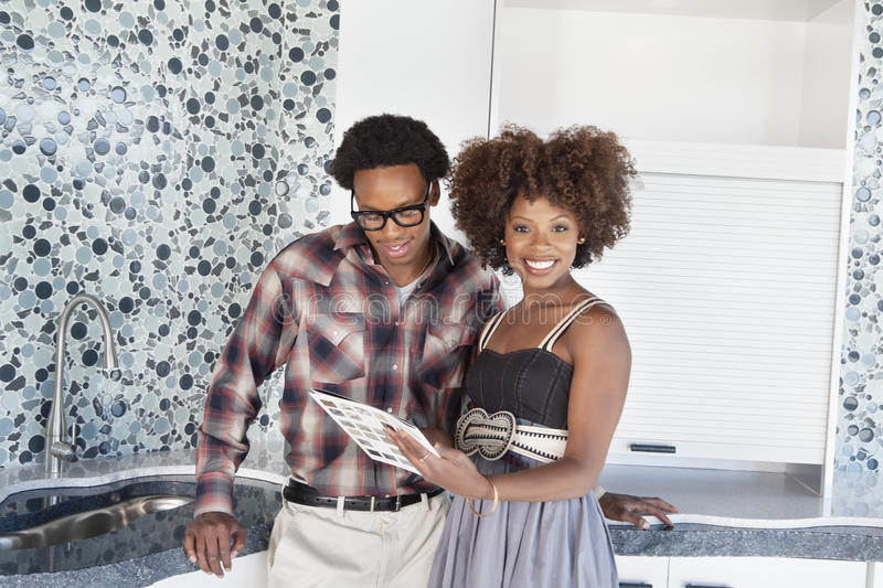 Portrait of young African American couple with color swatches in new kitchen royalty free stock photos