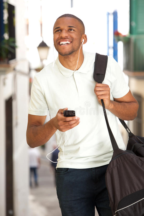 Young african american male traveler walking and listening music with mobile phone. Portrait of young african american male traveler walking outside and royalty free stock photos