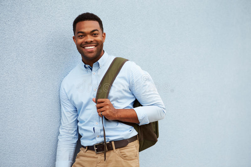 Portrait of young African American man against a grey wall royalty free stock image