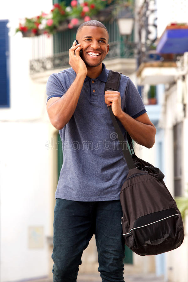 Young african american man with bag talking on smartphone. Portrait of young african american man with bag talking on smartphone royalty free stock photo