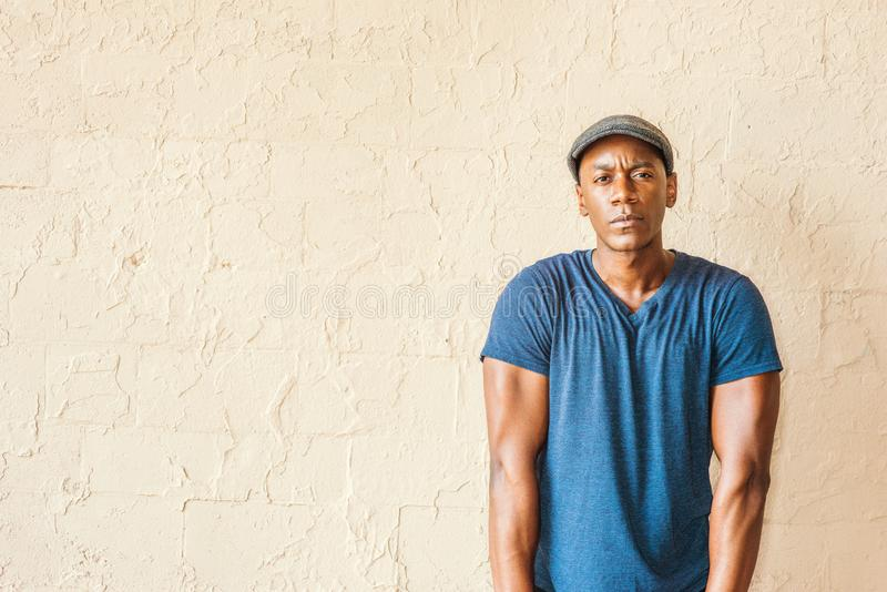 Portrait of Young African American Man in New York. A black guy wearing blue V neck T shirt, flat cap, straightening arms, shrugging shoulders, standing by stock photos