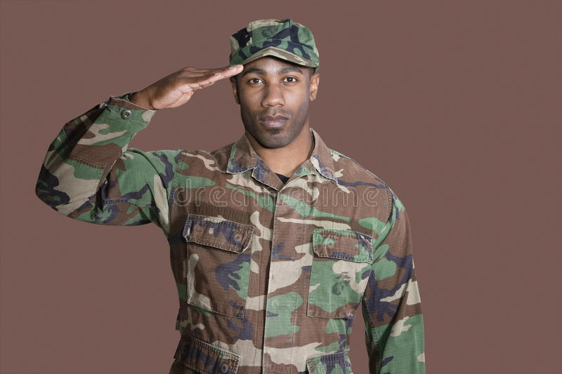 Portrait of a young African American US Marine Corps soldier saluting over brown background royalty free stock photo