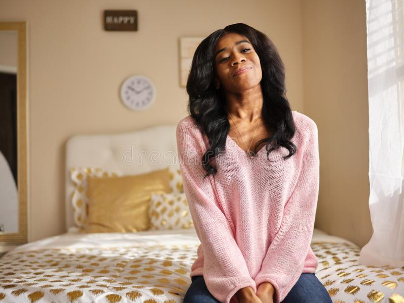 Portrait of young african american woman sitting on bed smiling royalty free stock photography