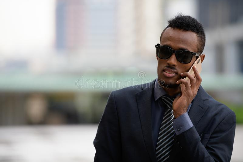 Young African businessman with sunglasses talking on the phone outdoors royalty free stock images