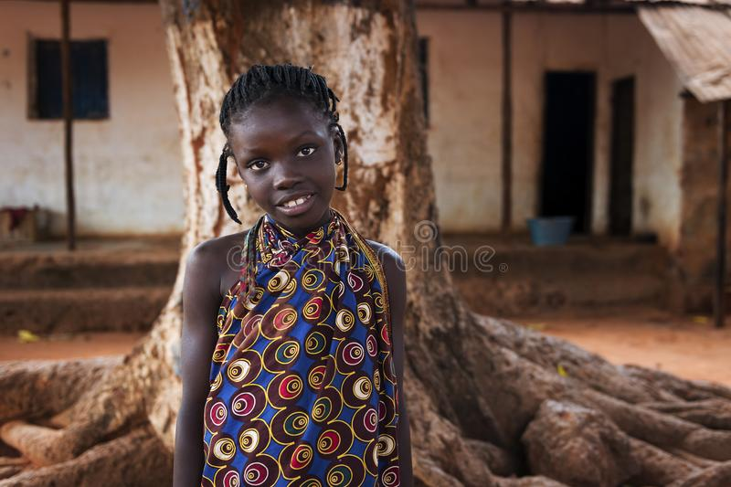 Portrait of a young african girl in front of her home in the town of Nhacra in Guinea Bissau. Nhacra, Republic of Guinea-Bissau - January 28, 2018: Portrait of a stock image