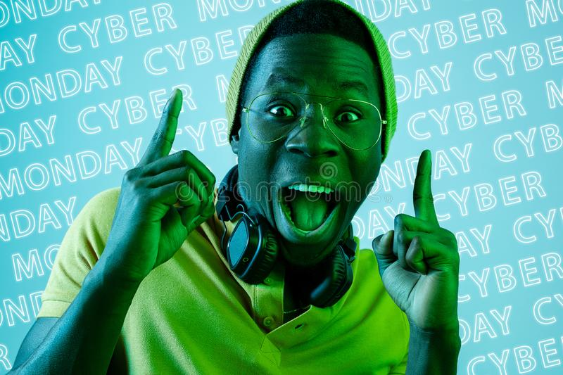 Portrait of young man on blue background, black friday. Portrait of young african man on blue background with neon lettering. Pointing up in green light. Concept stock photo