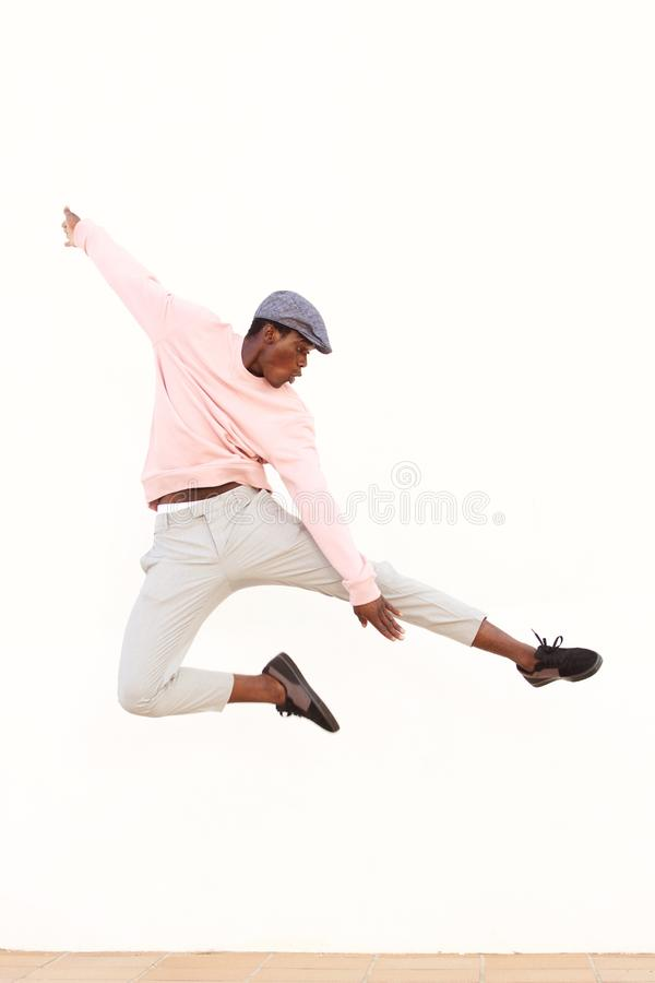 Young african man jumping in air on sidewalk outdoors stock image