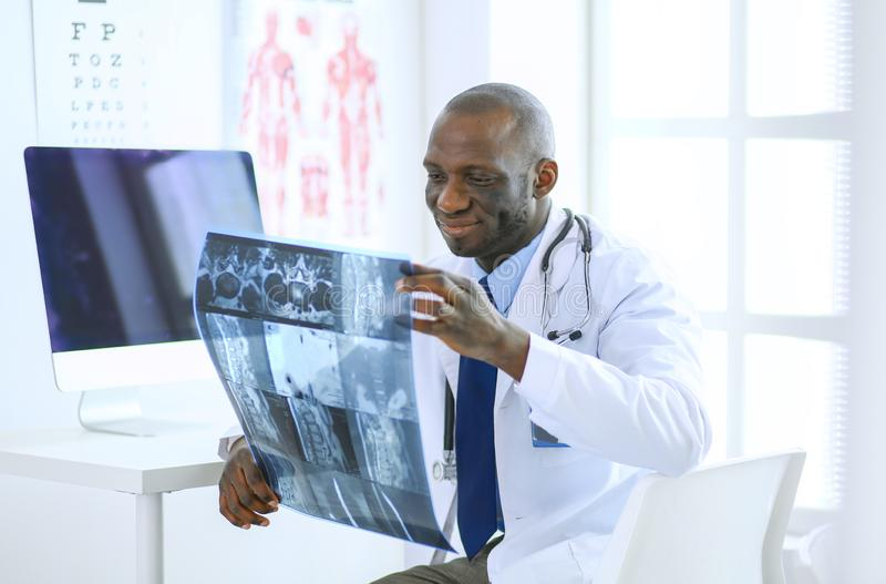 Portrait young african medical doctor holding patient`s x-ray stock image