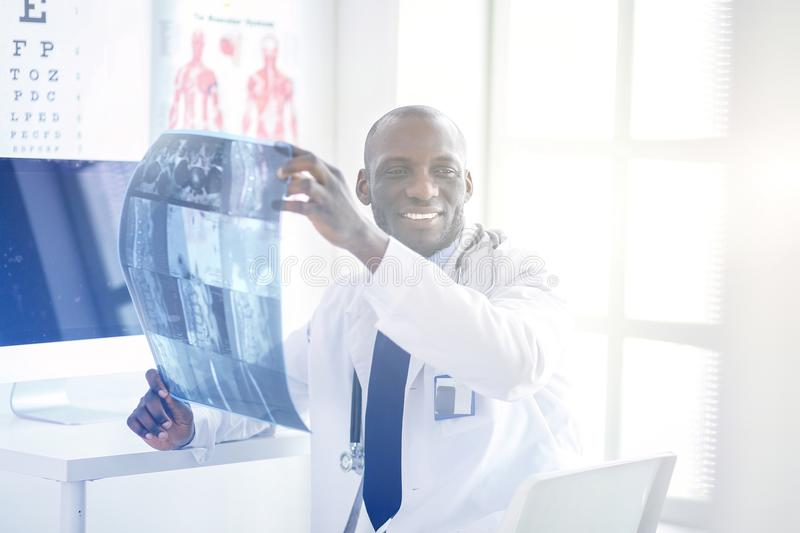 Portrait young african medical doctor holding patient`s x-ray stock images
