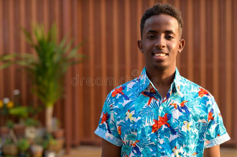 Face of happy young African tourist man with Afro hair smiling outdoors. Portrait of young African tourist man with Afro hair in the streets outdoors royalty free stock photo